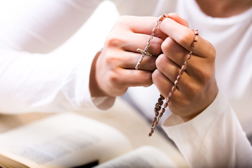 Woman praying, holding rosary beads